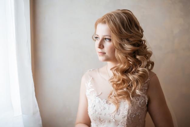 확대. 창문 가까이 서있는 웨딩 드레스에 젊은 여자. 휴일 및 이벤트