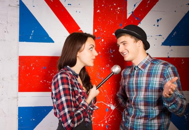 英国の旗のプリントの前で、マイクを使用してトレンディなファッションで幸せなハンサムな若い男にインタビューする若い女性を閉じます。