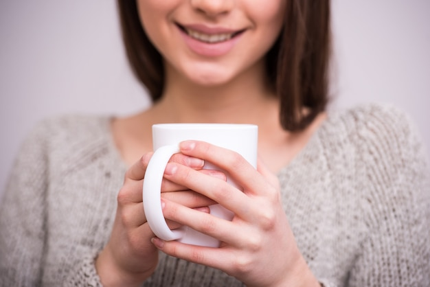 Close-up young woman is holding a cup of tea.