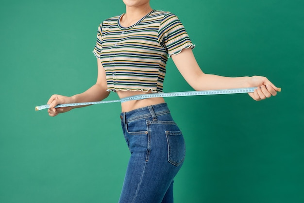 緑の上の巻尺で彼女の腰を測定する若い女性をクローズアップ