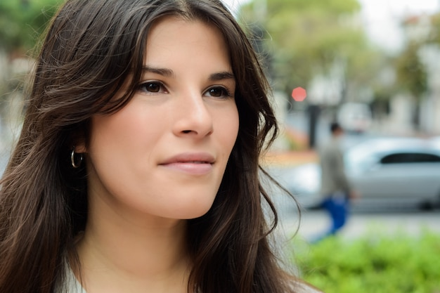 Close up of a young woman outdoors.