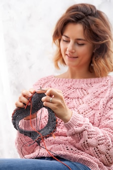 A close-up of a young woman in a pink cardigan knits with knitting needles from natural woolen threads