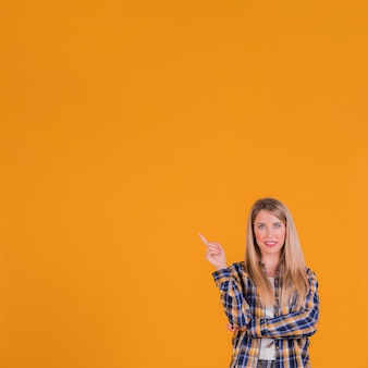 Close-up of a young woman pointing his finger upward against an orange backdrop