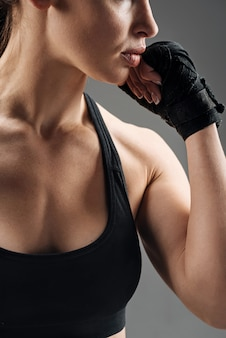 Close up of young woman posing with boxing gloves