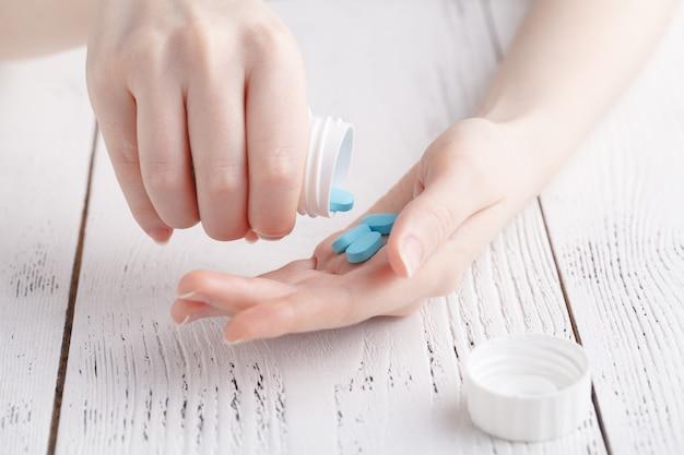 Крупным планом молодая женщина наливает таблетки из бутылки. концепция медицины и здравоохранения