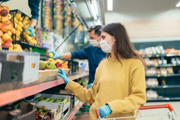 Close up. young woman in a protective mask buys apples