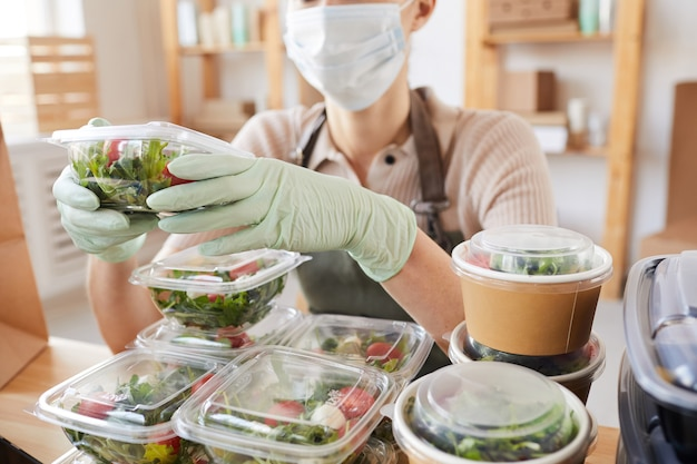 Close-up of young woman in protective mask and gloves packing fresh vegetables in boxes while sitting at the table