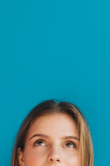 Close-up of young woman's face looking up against blue backdrop