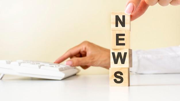 白いテーブルの床、背景に白いキーボードのニュースの文言のための白いシャツの木製のブロックキューブで若い女性の手を閉じます。財務、マーケティング、ビジネスの概念