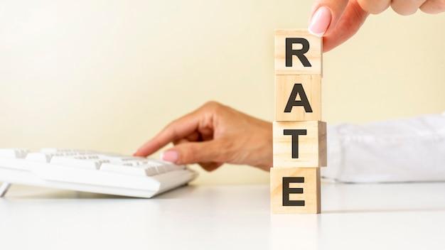 흰색 테이블 바닥에 rate 문구, 배경에 흰색 키보드에 대한 흰색 셔츠 나무 블록 큐브에 젊은 여성의 손을 닫습니다. 금융, 마케팅 및 비즈니스 개념