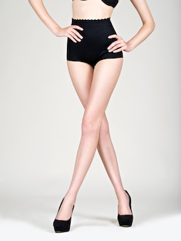 Primo piano delle gambe della giovane donna in scarpe nere a tacco alto