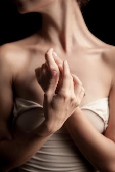 Il primo piano del collo e delle mani di una giovane donna su sfondo scuro