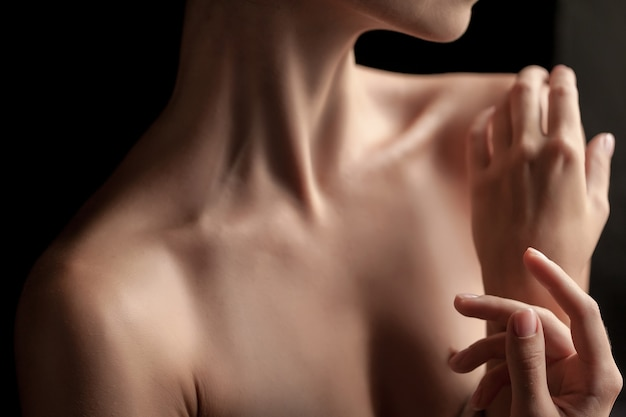 The close-up of a young woman's neck and hands  on dark background