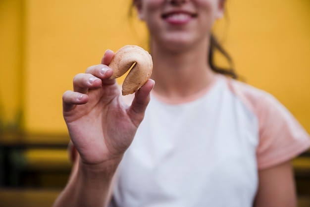 Close-up of a young woman showing fortune cookie in front of camera