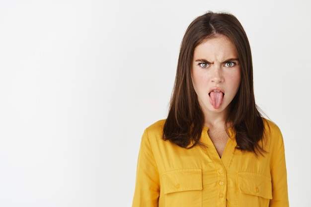 Close-up of young woman showing tongue and disappointment, frowning upset, staring at something disgusting, express dislike while standing over white wall.