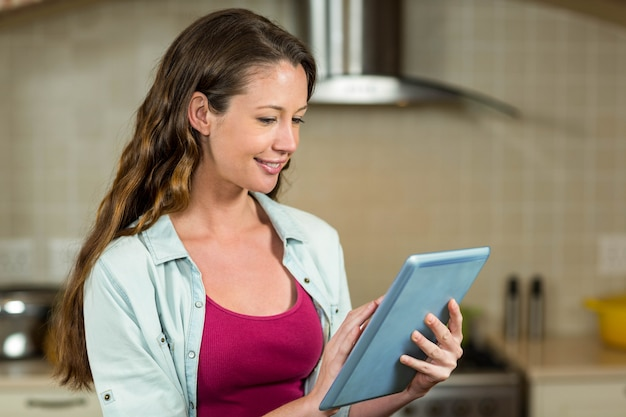 Close-up of young woman sitting on worktop and using tablet
