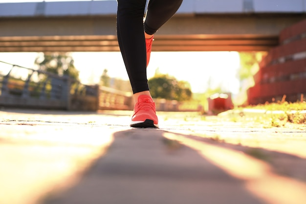 Close up of young woman in sports shoes jogging while exercising outdoors.