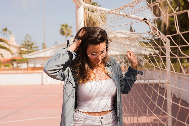 Close-up of a young woman standing near the soccer goal net