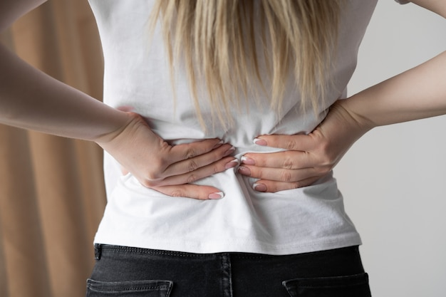 Close up of young woman suffering from back pain, standing by the window at home