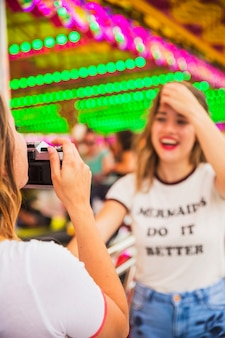 Close-up of young woman taking picture of her friend