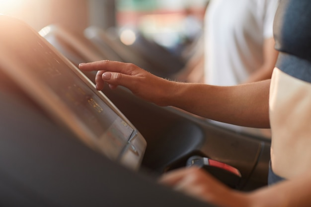 Close-up of young woman touching the screen o treadmill during her sports training