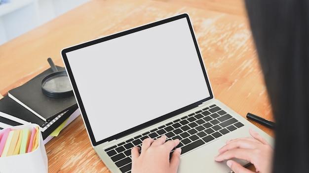 빈 화면이 랩톱 컴퓨터를 입력하는 근접 젊은 여자