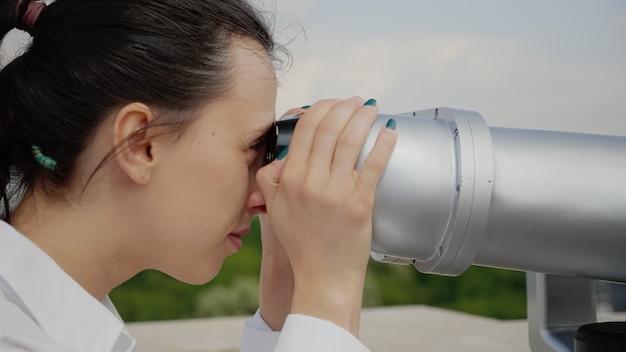 Primo piano di una giovane donna che usa il binocolo per visitare la città