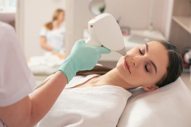 Close up of young woman visiting professional cosmetician and having modern laser hair removal procedure on her face