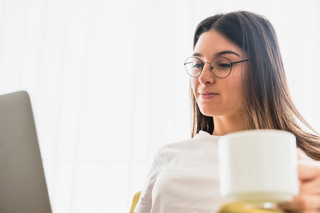 Close-up of young woman wearing eyeglasses holding coffee cup using laptop