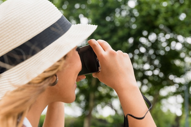 Close-up of young woman wearing hat taking photograph from camera