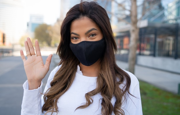 Close-up of young woman wearing protective mask and wave hand to say hello while standing outdoors on the street. urban concept.