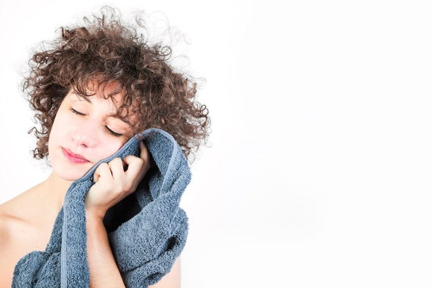 Close-up of young woman wipes her face with towel isolated on white background