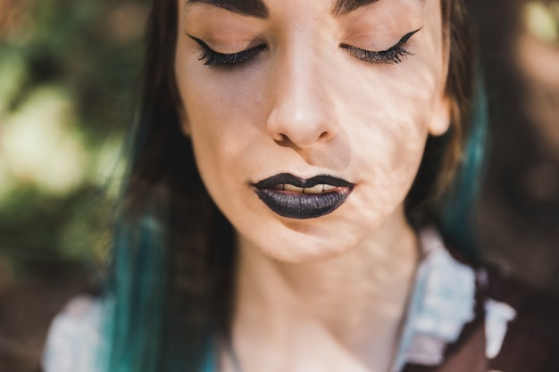 Close-up of young woman with black lipstick on her lips