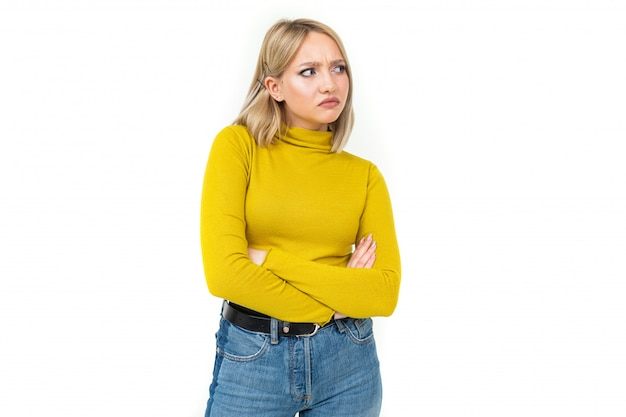 Close-up of a young woman with blonde hairstyle dressed in jeans and a yellow sweater with an indignant look on her face on a white isolated background