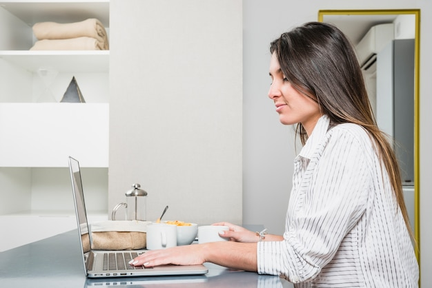 Close-up of young woman with breakfast on table using laptop