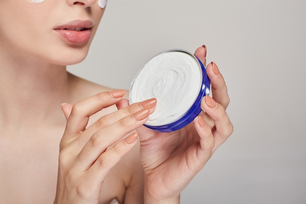 Close-up of a young woman with clean skin holds a cream in both hands in a blue jar. spa and skin care.