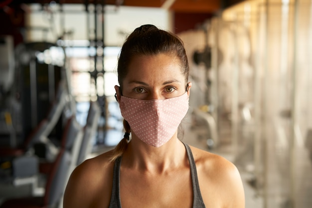 Close up of young woman with face mask looking at camera in gym.