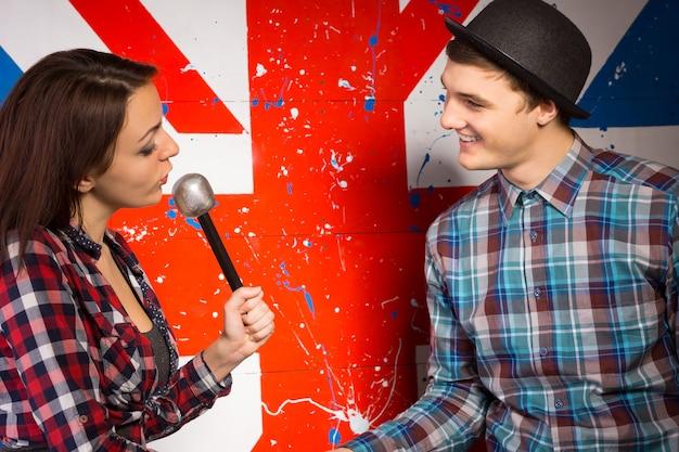 巨大な英国の旗のプリントの前で笑顔の男と話しているマイクで若い女性を閉じます。 Premium写真
