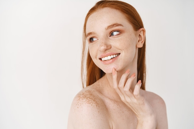 Close-up of young woman with pale skin and freckles standing naked on white wall, turn left, smiling white teeth and touching perfect no acne face