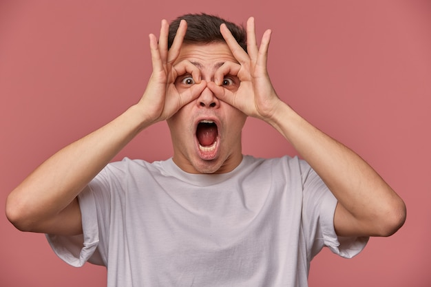 Close up of young wondered guy wears in blank t-shirt, looks thought okay gestures, make masks with fingers, stands on pink with shocked expression.
