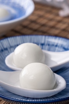 Close up of yuanxiao tangyuan (glutinous rice dumpling balls) in a bowl on gray table with flower, food for chinese lantern yuanxiao festival.