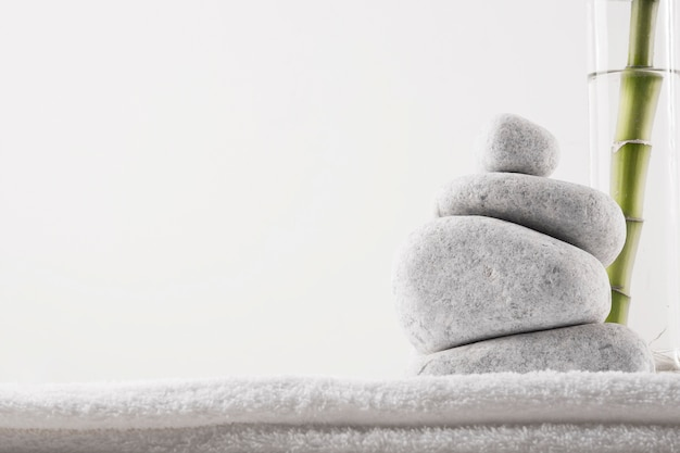 Close-up of zen stones and bamboo plant in vase on white towel isolated on white background