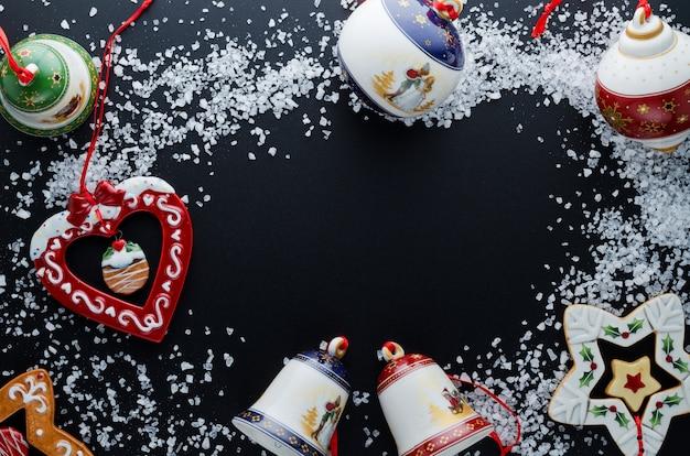 Елочные украшения (шары, колокольчики, сердце, звезда) в снегу (большая морская соль) на черном фоне. close-up. свободное место для текста. вид сверху.