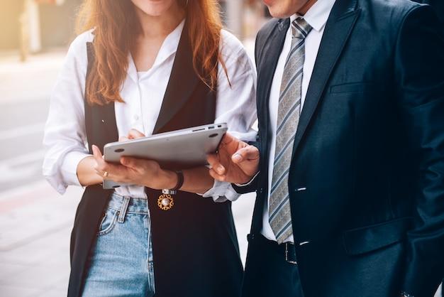 Close up деловые люди, идущие в деловом районе и рассказывающие о новом деловом сотрудничестве и маркетинговом плане на открытом воздухе