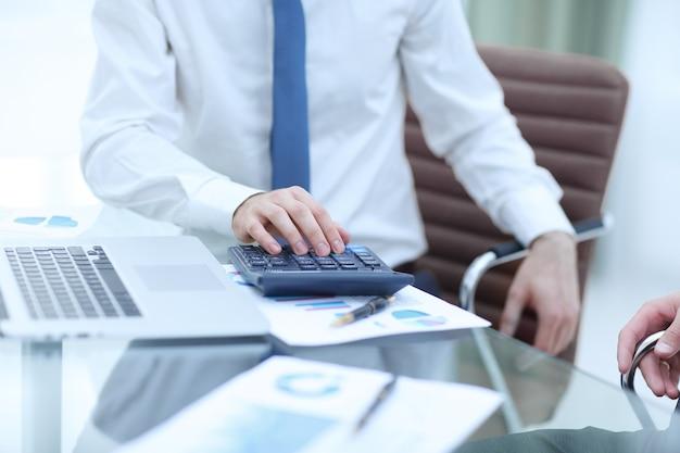 クローズアップビジネスマンは、金銭的利益を計算するために計算機を使用します