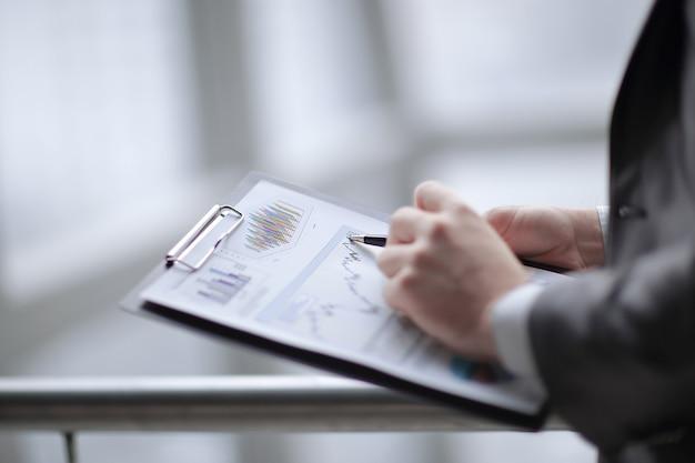 Close upbusinessman checking sales schedulephoto on blurred background