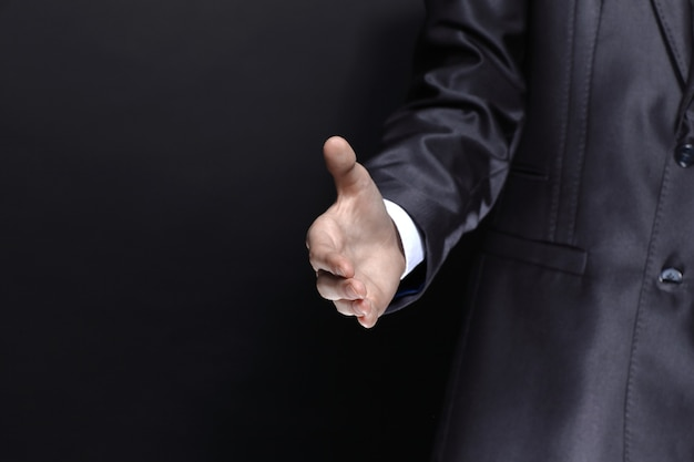Close upbusinessman hand out for a handshakeisolated on black background