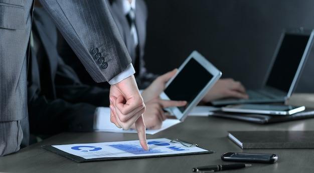 재무 보고서에서 손가락을 가리키는 사업가를 닫습니다.