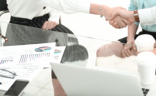 Крупным планом финансовые партнеры пожимают друг другу руки, сидя за столом