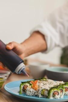 병으로 손을 닫고 스시 접시 음식 배달 개념에 소스를 추가합니다